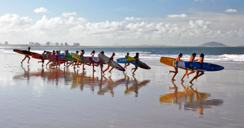 Group of surfers carrying surfboards down towards the sea