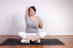 overweight-woman-exercising-stretching-home-22755791